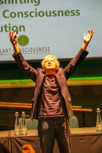 John Perkins beginning his talk with some group energising breathing exercises. Picture taken by Boris Austen