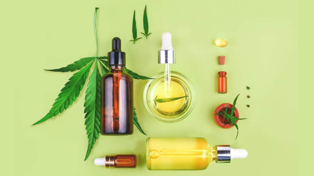 cbd oil bottles and cannabis leaf on a green table